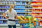a woman is overwhelmed with the wide range in the supermarket when shopping.