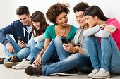 Group Of Happy Young Friends Looking At Cell Phone
