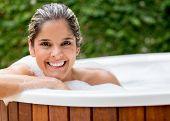 Happy woman taking a bath in the hot tub
