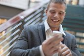 Happy businessman with smartphone on hand, blurred background, business building interior
