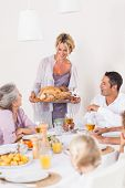 Proud mother bringing turkey to dinner table at thanksgiving