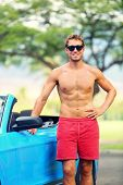 Handsome man with sports car. Well built fit young male model standing shirtless leaning on the door of a blue sports car smiling at the camera.