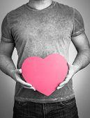 Human hands holding a pink heart shape
