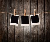 Three blank instant photos hanging on the clothesline. On old wood background.