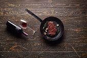 Marbled beef steak in a grill pan with a bottle of wine and wine glass on old wood background. Juicy