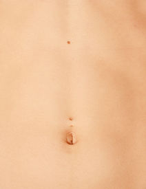 image of pierced belly button  - close up shot of a beauty woman belly - JPG