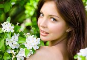 Portrait of pretty girl near the blossomed tree in the park. Concept of youth and natural beauty