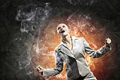 businesswoman in anger screaming against dark grey background
