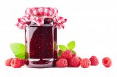 Jar with raspberry jam with raspberries on white