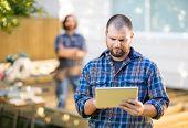 Mid adult manual worker using digital tablet with coworker standing in background at construction site