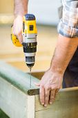 stock photo of hand drill  - Cropped image of carpenter - JPG