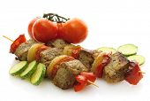 tasty grilled meat and vegetables on skewers, isolated on white