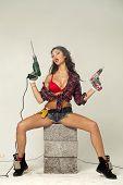 High fashion glamour model in Daisy duke shorts, tool belt, red bra with a screw gun