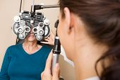 Optometrist examining eyes of senior woman with a phoropter