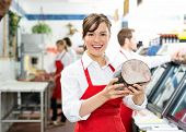 Portrait of happy female butcher holding ham at store with colleagues working in background