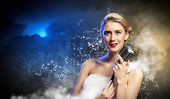 Image of female blonde singer holding microphone against smoke background