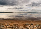 Rocky Beach Fronts Lake Reflecting Dramatic Skies In Finnish Lapland.