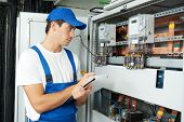 stock photo of fuse-box  - Young adult electrician builder engineer inspecting electric counter equipment in distribution fuse box - JPG
