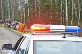 stock photo of flashers  - police car with a flasher in front of damaged lorry trailer in ditch of highway - JPG