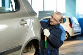 pic of peen  - auto repair man worker flatten and align metal body car with hammer in automotive industry - JPG