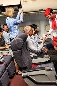 stock photo of cabin crew  - Flight attendant check passenger tickets in plane cabin - JPG