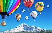 stock photo of air transport  - colourful air balloons on blue sky and mountains in the background - JPG