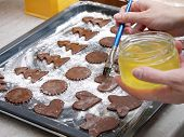 Christmas gingerbread cookies cut out from raw pastry being brushed with egg white