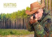The hunter with hunting rifle aiming at you. Safety and insurance concept. Picture with space for your text.