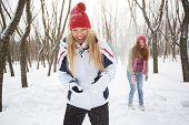 Portrait of happy girl in winterwear laughing on background of her friend outside
