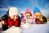 Joyful kids in winterwear lying in snowdrift and laughing