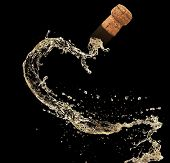 Cork of champagne in splash, isolated on black background