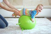 stock photo of gymnastic  - Baby playing with gymnastic ball with mother at home - JPG