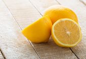 foto of vegetarian meal  - Fresh lemons on white wooden background. Selective focus.