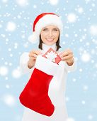 christmas, x-mas, winter and happiness concept - smiling woman in santa helper hat with small gift b