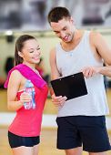 fitness, sport, training, gym and lifestyle concept - smiling male trainer with clipboard and woman