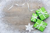 picture of gift wrapped  - Gift boxes with bow and snowflakes on wooden background - JPG