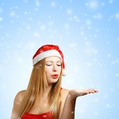 Young Woman In Santa Hat Blows On Open Hand
