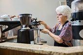 Senior female barista making coffee in cafe