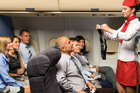 picture of cabin crew  - Flight attendant safety demo fastening seat belt passenger airplane cabin - JPG