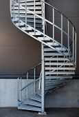 image of spiral staircase  - Modern metal spiral staircase above dark gray wall - JPG