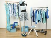 Dressing closet with blue clothes arranged on hangers and an outfit on a mannequin.