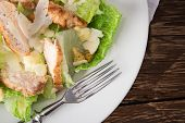 stock photo of caesar salad  - Caesar salad with chicken and greens on wooden table - JPG