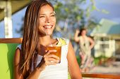 Woman drinking alcohol Mai Tai drink on Hawaii at beach club at sunset. Beautiful girl enjoying alco