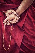 Vintage retro effect filtered hipster style travel image of Tibetan Buddhism - prayer beads in Buddhist monk hands with grunge texture overlaid. Ladakh, India