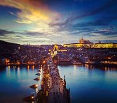 Vintage retro hipster style travel image of night aerial view of Prague castle and Charles Bridge ov