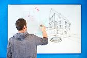 Young architect, drawing ideas, plans and concepts in an isometric perspective on a white board