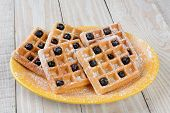 Closeup of a plate of waffles and blueberries. The plate is on a rustic farmhouse style table and th