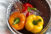pic of yellow-pepper  - Yellow red and orange bell peppers washed in stainless steel metal colander - JPG