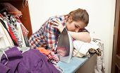 Exhausted Woman Ironing Big Pile Of Clothes