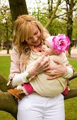 Beautiful Young Mother And Baby Daughter Having Fun Outdoors At Springtime